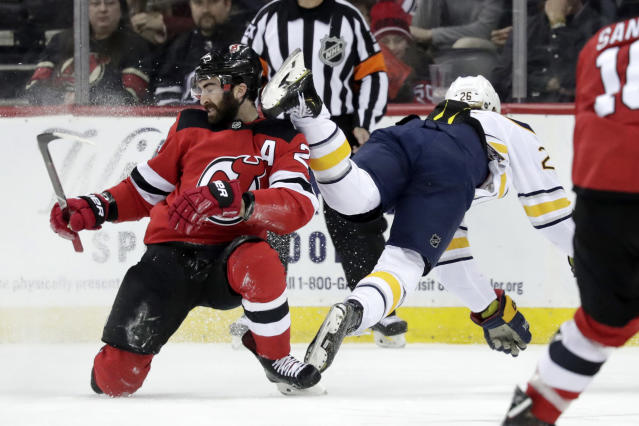 Buffalo Sabres defenseman Rasmus Dahlin, right, of Sweden, trips over New Jersey Devils right wing Kyle Palmieri during the first period of an NHL hockey game, Monday, March 25, 2019, in Newark, N.J. (AP Photo/Julio Cortez)