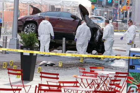 Emergency personnel inspect a vehicle involved in striking a number of pedestrians in Times Square in New York