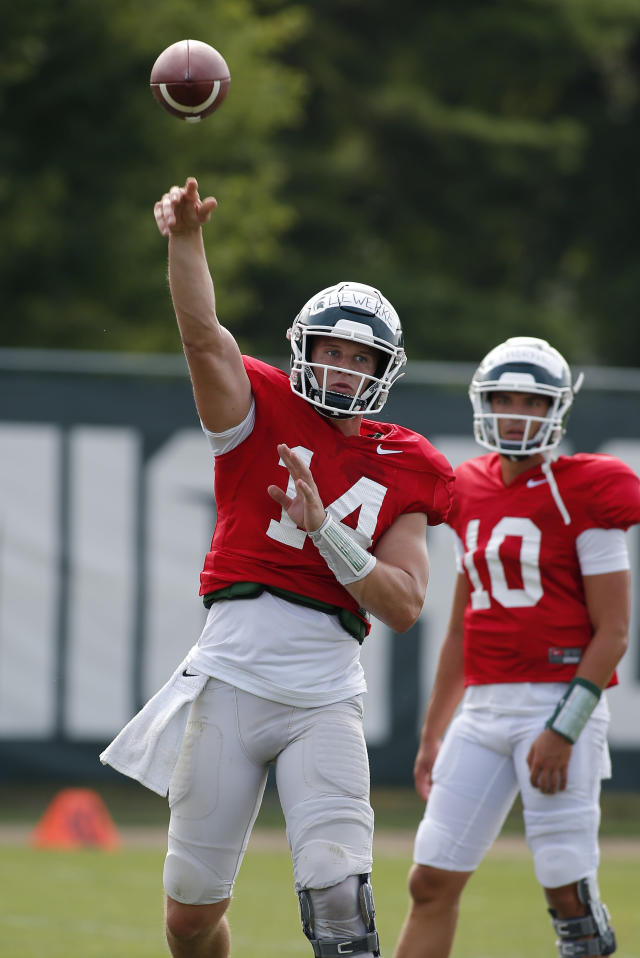 Michigan State quarterback Brian Lewerke, left, throws a pass during an NCAA college football practice, Monday, Aug. 12, 2019, in East Lansing, Mich. (AP Photo/Al Goldis)