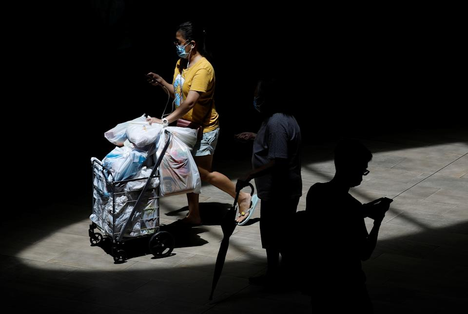 A woman pushes her grocery cart, as she leaves a supermarket during the coronavirus disease outbreak in Singapore on 28 September, 2021. (PHOTO: Reuters)