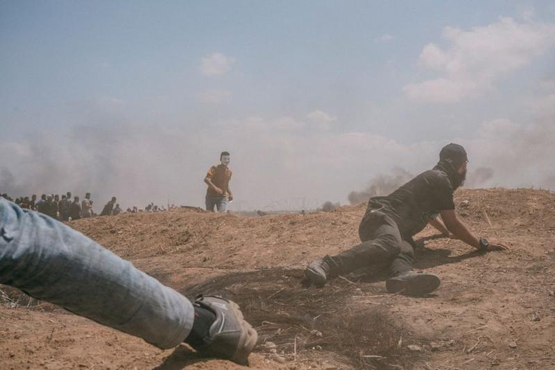 A man hides behind an embankment during the protest along the Gaza-Israel border.