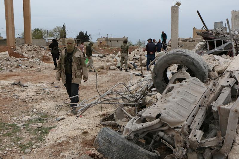 Rebel fighters walk through the rubble following an alleged bombing by Islamic State in Marea, northern Aleppo on April 8, 2015 (AFP Photo/Zein al-Rifai)