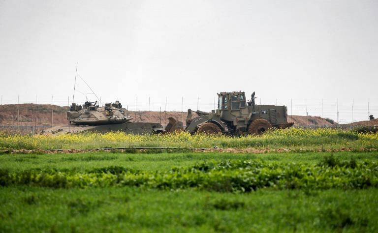 An Israeli tank and a bulldozer are seen along the border fence between Israel and the Gaza Strip where the army says troops shot dead a Palestinian suspected of placing a bomb near the barrier (AFP Photo/Said KHATIB)