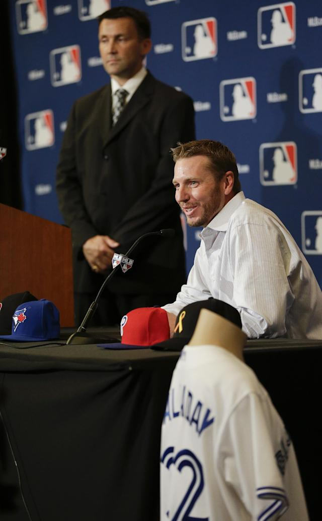 Two-time Cy Young Award winner Roy Halladay, seated, speaks during a news conference announcing his retirement after 16 seasons in the major leagues with Toronto and Philadelphia at the MLB winter meetings in Lake Buena Vista, Fla., Monday, Dec. 9, 2013. Jay Stenhouse, vice president of communications with the Toronto Blue Jays, is at back left. (AP Photo/John Raoux)