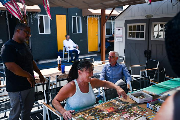 Members of the motel community work on a puzzle and converse inside the Reno Motel in Mid-City, Los Angeles on August 5, 2019.