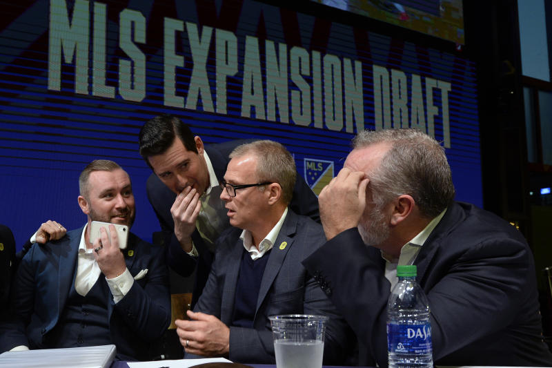FILE - In this Nov. 19, 2019, file photo, from left, Nashville SC assistant general manager, Ally MacKay, general manager Mike Jacobs, head coach Gary Smith, and CEO Ian Ayre talk before making the team's first selection during the Major League Soccer expansion draft  in Nashville, Tenn. Nashville SC opens their inaugural MLS season on Saturday.  (AP Photo/Mark Zaleski, File)