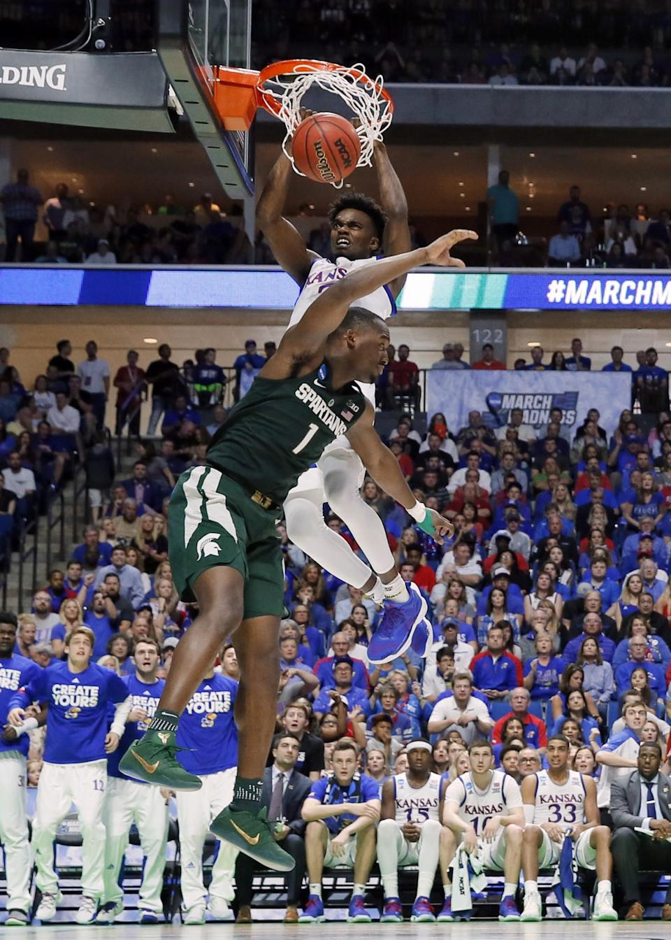 <p>Kansas guard Lagerald Vick (2) dunks the ball over Michigan State' Joshua Langford (1) in the second half of a second-round game in the men's NCAA college basketball tournament in Tulsa, Okla., Sunday, March 19, 2017. (AP Photo/Tony Gutierrez) </p>