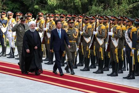 Iranian President Hassan Rouhani walks with Japan's Prime Minister Shinzo Abe, during a welcome ceremony in Tehran