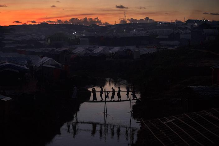 <p>People cross a bamboo bridge over a stream as the sun sets on October 13, 2017 at the Kutuplaong refugee camp, Cox's Bazar, Bangladesh. (Photograph by Paula Bronstein/Getty Images) </p>