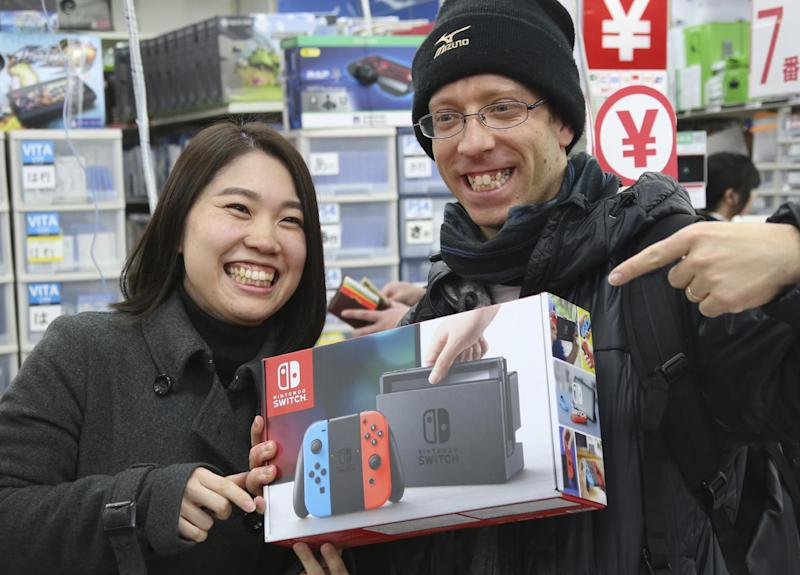 "David Flores, 34 years old, right, and his wife Nao Imoto, 31 years old, show off Nintendo's newest computer game consoles ""Switch"" at a retail store Bic Camera in central Tokyo. Friday, March 3, 2017. (AP Photo/Koji Sasahara)"