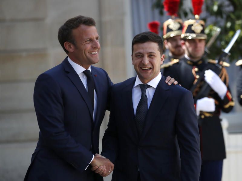 FILE In this file photo taken on Monday, June 17, 2019, French President Emmanuel Macron, right, greets Ukrainian President Volodymyr Zelenskiy before a meeting at the Elysee Palace, in Paris, France. Ukraine's president sits down Monday, Dec. 9, 2019 for peace talks in Paris with Russian President Vladimir Putin in their first face-to-face meeting, and the stakes could not be higher. More than five years of fighting in eastern Ukraine between government troops and Moscow-backed separatists has killed more than 14,000 people, and a cease-fire has remained elusive. (AP Photo/Christophe Ena, File)