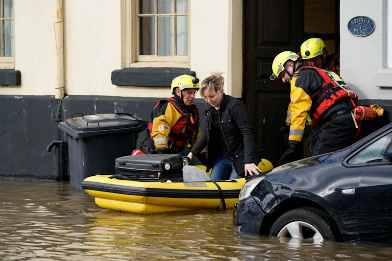 Rescue workers help a woman to safety in flood waters in Bewdley, where river levels could break a 20-year record as rain continues to fall: Getty Images