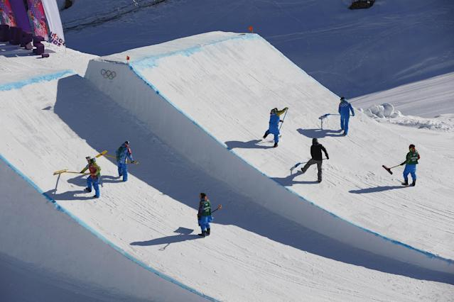 Workers groom a jump during a break in the women's snowboard slopestyle qualifying at the Rosa Khutor Extreme Park ahead of the 2014 Winter Olympics, Thursday, Feb. 6, 2014, in Krasnaya Polyana, Russia. (AP Photo/Sergei Grits)