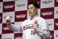 Former New York Yankees pitcher Masahiro Tanaka on his new uniform poses for a photo session during a news conference Saturday, Jan. 30, 2021 in Tokyo. Tanaka returned to Japan to rejoin the Rakuten Golden Eagles in the Nippon Professional Baseball League. (AP Photo/Eugene Hoshiko)