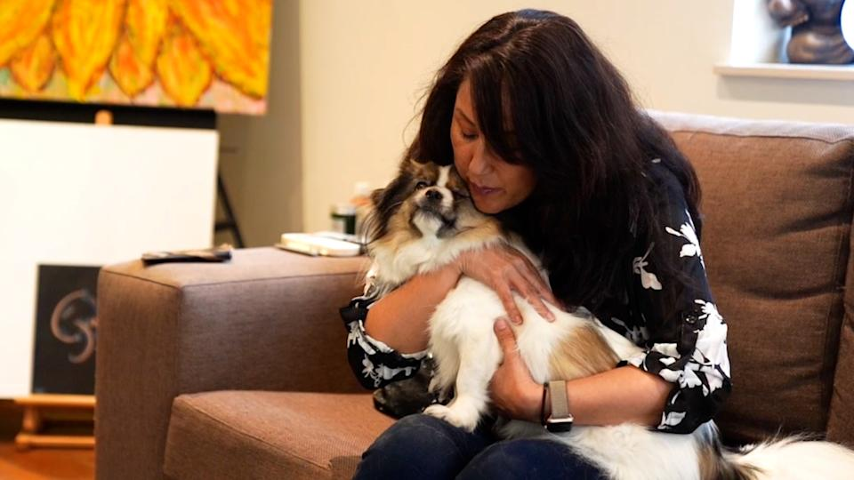 Simone Lee sits on a couch and holds Tibetan spaniel Dexter on her lap.