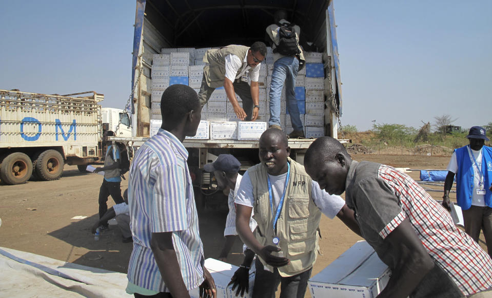 In this photo released by the World Food Programme (WFP), WFP staff and helpers unload a truck of cereal food assistance at a U.N. compound where many displaced have taken shelter in Juba, South Sudan, Tuesday, Dec. 24, 2013. South Sudan's military spokesman says there is increasing tension at a United Nations camp in the rebel-held city of Bor because armed elements have entered the congested area where the U.N. says about 17,000 civilians are seeking protection. (AP Photo/WFP, George Fominyen)