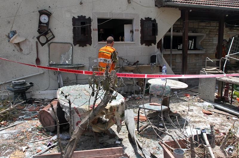 An Israeli soldier inspects the damage at an house that was hit by a rocket fired by militants from the Gaza Strip, on July 22, 2014, in the Israeli town of Yahud (AFP Photo/Gil Cohen Magen)