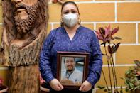 Ariadna Bautista holds a picture of her late husband Diego Gutierrez, who died from Covid-19 even though he avoided leaving home
