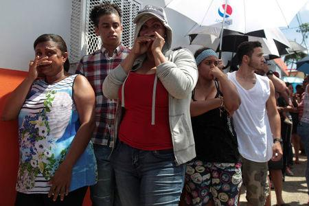 People wait in line for aid items to be handed out in San Juan. REUTERS/Alvin Baez