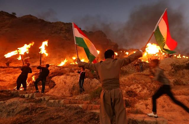 <p>Iraqi Kurds wave Kurdish flags and hold burning torches as they walk up a mountain during a gathering to show support for the upcoming independence referendum and encourage people to vote in the town of Akra, some 300 miles north of Baghdad on Sept. 10, 2017. Iraq's autonomous Kurdish region will hold a historic referendum on statehood in Sept. 25, 2017, despite opposition to independence from Baghdad and possibly beyond. (Photo: Safin Hamed/AFP/Getty Images) </p>
