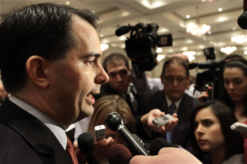 Wisconsin Gov. Scott Walker is surrounded by the news media after speaking to the Illinois Chamber of Commerce Tuesday, April 17, 2012 in Springfield, Ill. Ever since his fight to pass an anti-union bill last year, Walker has kept up a jet-setting schedule that's more akin to a candidate running for president than governor. (AP Photo/Seth Perlman)