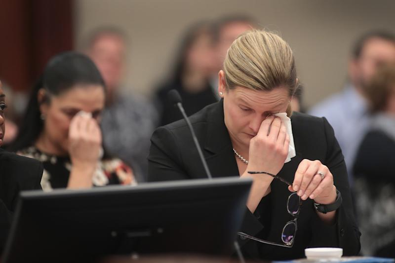 Gina Nichols, mother of victim Maggie Nichols, and Assistant Attorney General Angela Povilaitis wipe tears from their eyes as they listen to Gwen Anderson deliver a victim impact statement. (Scott Olson/Getty Images)