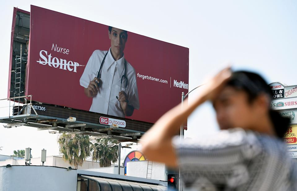 This May 9, 2018 photo shows a billboard for MedMen, a marijuana dispensary, at an intersection in Los Angeles. MedMen recently rolled out an ad campaign that featured photos of 17 people including a white-haired grandmother, a schoolteacher, a business executive, a former pro football player and a nurse, being splashed across billboards, buses and the web. (AP Photo/Chris Pizzello)