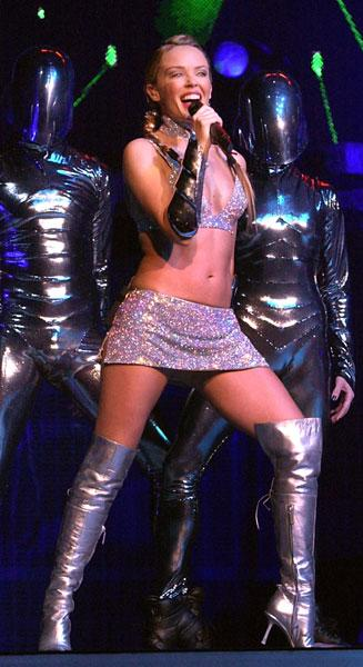 <b>Kylie on her Fever tour, 2002</b><br><br>Proving that even the top stars recycle their favourite items, Kylie wore her silver boots again - this time teaming them with a silver sparkly bikini and mini skirt... as you would.