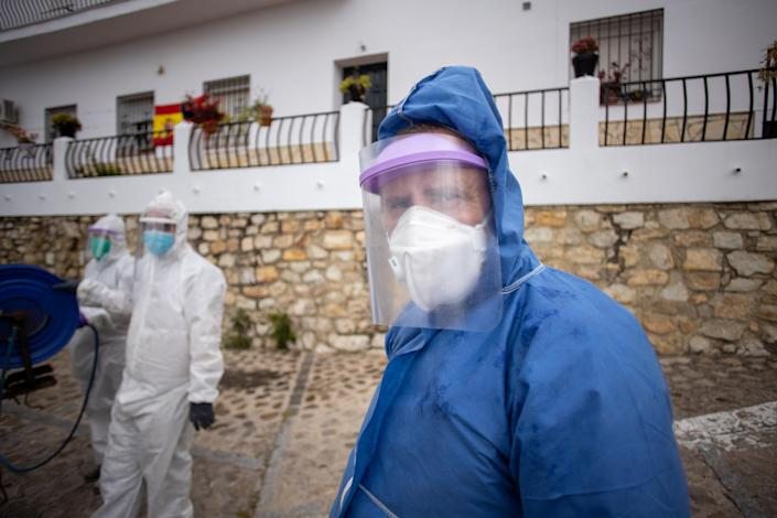 Volunteers look on as they disinfect the streets of Zahara de la Sierra, Spain. (Getty Images)