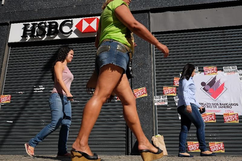 People walk in front of a closed HSBC bank branch, following the nank's announcement to close HSBC Brazil at Cinelendia square, downtown Rio de Janeiro on June 9, 2015 (AFP Photo/Christophe Simon)