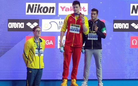 China's Sun Yang, centre, holds up his gold medal as silver medalist Australia's Mack Horton, left, stands away from the podium with bronze medalist Italy's Gabriele Detti right, after the men's 400m freestyle final at the World Swimming Championships in Gwangju, South Korea - Credit: AP