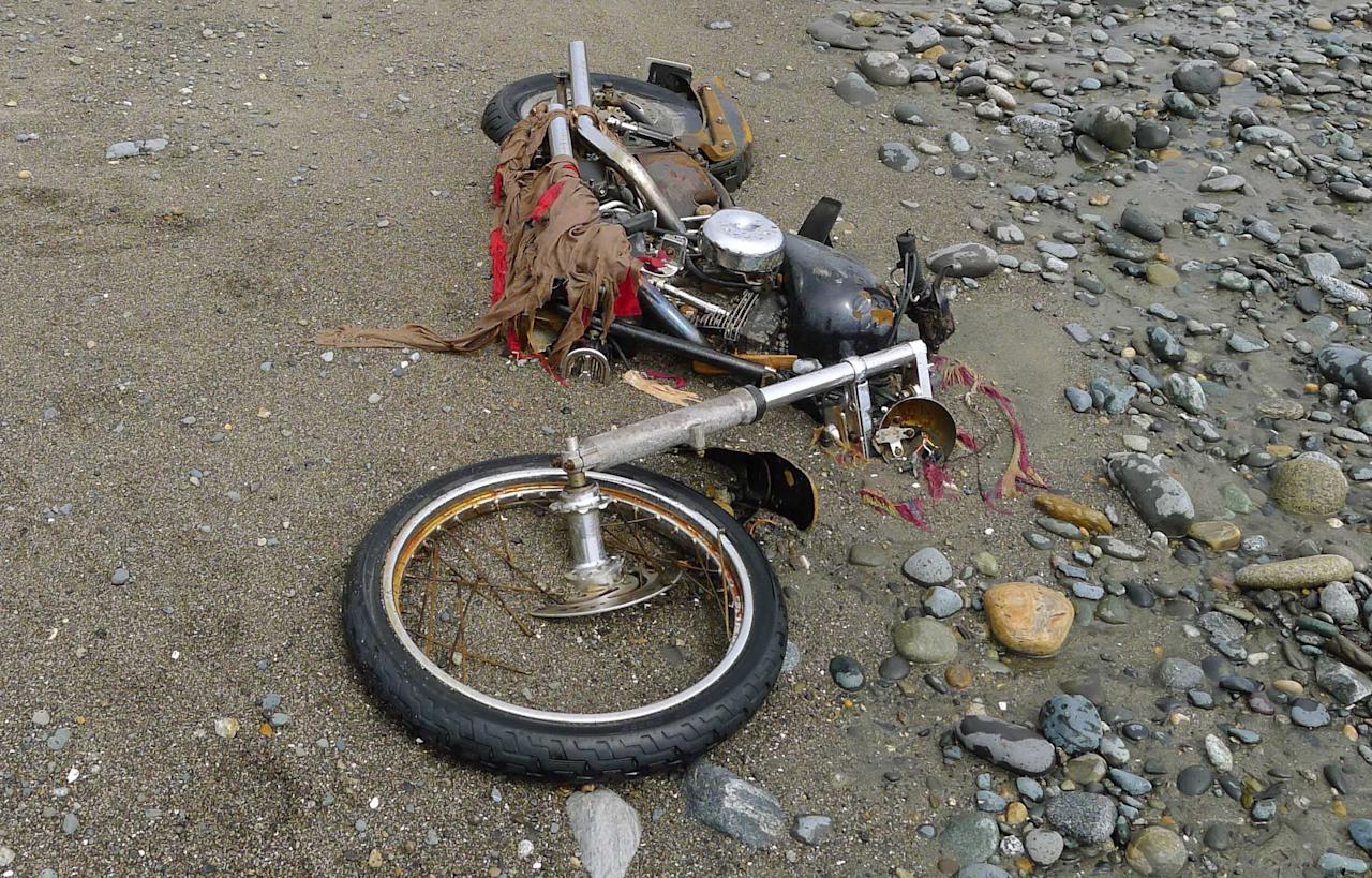 In this photo taken by Canadian Peter Mark in the end of April, 2012, and released on Wednesday, May 2, a Harley-Davidson motorbike lies on a beach in Graham Island, western Canada. Japanese media say the motorcycle lost in last year's tsunami washed up on the island about 6,400 kilometers (4,000 miles) away. The rusted bike was originally found by Mark in a large white container where its owner, Ikuo Yokoyama, had kept it. The container was later washed away, leaving the motorbike half-buried in the sand. Yokoyama, who lost three members of his family in the March 11, 2011, tsunami, was located through the license plate number, Fuji TV reported Wednesday. (AP Photo/Kyodo News, Peter Mark)