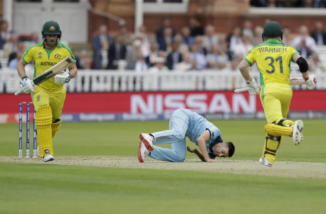 England's Mark Wood goes to ground after pitching a delivery as Australia's captain Aaron Finch, left, and Australia's David Warner add runs during the Cricket World Cup match between England and Australia at Lord's cricket ground in London, Tuesday, June 25, 2019. (AP Photo/Matt Dunham)