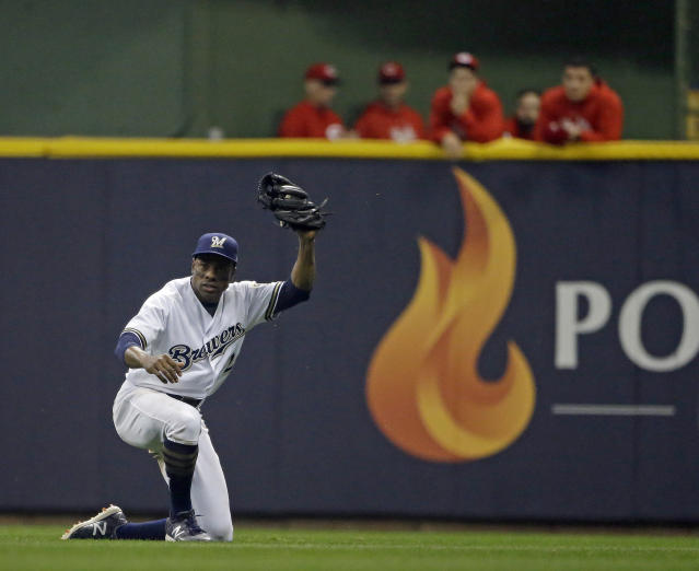 FILE - In this Sept. 18, 2018 file photo, Milwaukee Brewers' Curtis Granderson raises his glove after making a sliding catch in the outfield during the fifth inning of a baseball game against the Cincinnati Reds in Milwaukee. Granderson has agreed to a minor league contract with the Miami Marlins and will report to big league spring training. If added to the 40-man roster, he would get a one-year contract that pays $1.75 million while in the major leagues and have the chance to earn $250,000 in performance bonuses for plate appearances. (AP Photo/Aaron Gash, File)