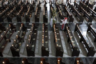 A Catholic priest walks beside empty pews with lighted candles as he prepares for an online mass to prevent the spread of the coronavirus at the Saint Peter Parish Church in Quezon city, Philippines on Palm Sunday, March 28, 2021. The government banned religious activities during the Holy Week as it enters into stricter lockdown measures starting next week while the country struggles to control an alarming surge in COVID-19 cases. (AP Photo/Aaron Favila)