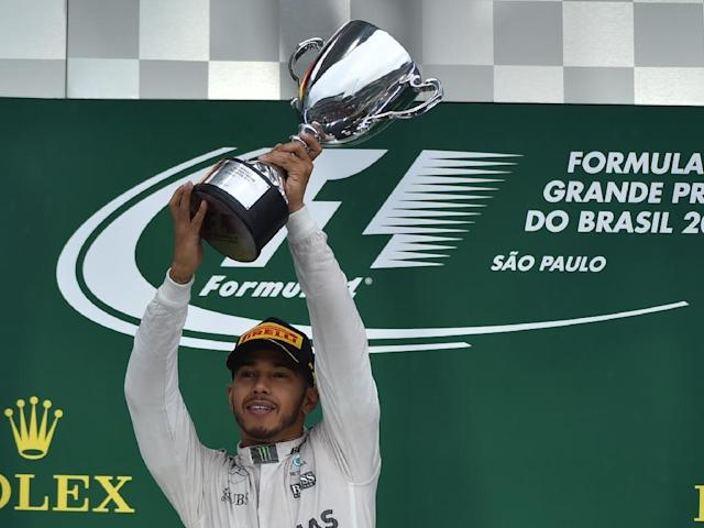 Mercedes driver Lewis Hamilton celebrates with the trophy after winning the Brazilian Grand Prix on November 13, 2016 (AFP Photo/Miguel Schincariol)
