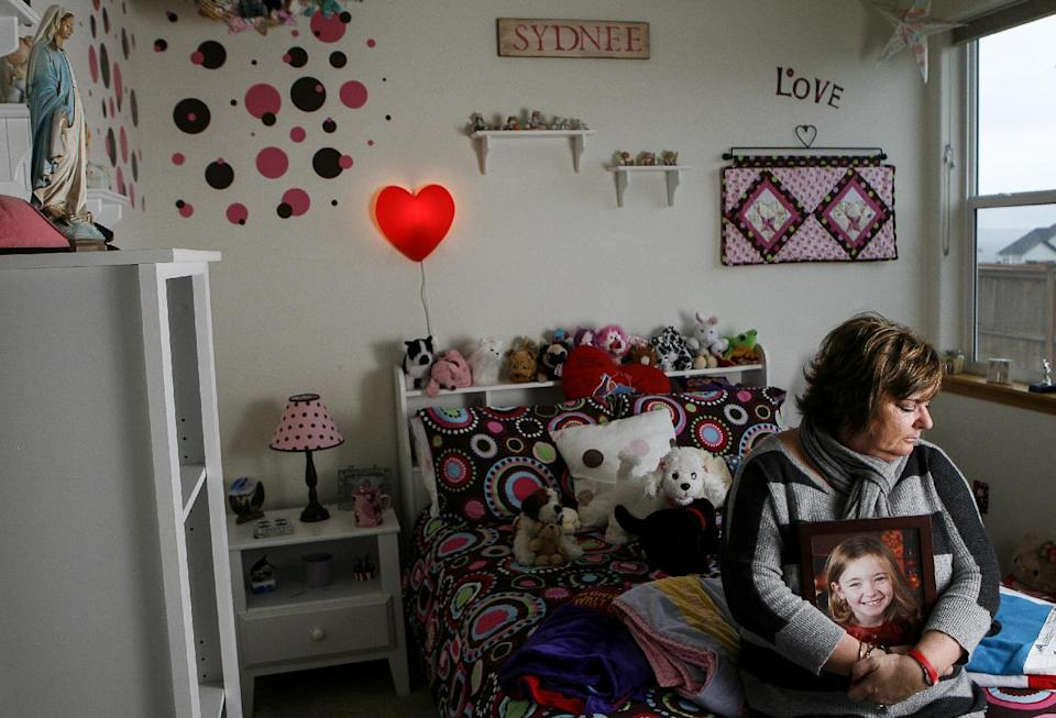 In this Saturday, Dec. 22, 2012 photo, Judy Neiman holds a photo of her daughter, Sydnee, in her bedroom at their home in West Richland, Wash. Sydnee died in late 2011 after Neiman accidentally backed over her with her SUV. Although there is a law in place that calls for new manufacturing requirements to improve the visibility behind passenger vehicles, the standards have yet to be mandated because of delays by the U.S. Department of Transportation. (AP Photo/Kai-Huei Yau)
