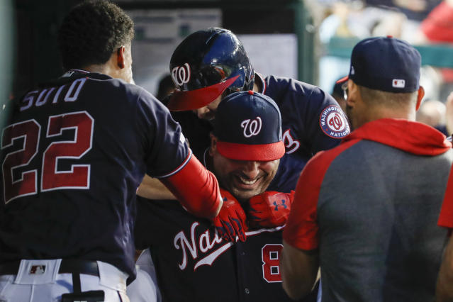 Washington Nationals' Brian Dozier, top back, gets a piggyback ride from Ali Modami as they celebrate Dozier's solo home run during the fourth inning of the team's baseball game against the Cincinnati Reds at Nationals Park, Tuesday, Aug. 13, 2019, in Washington. (AP Photo/Alex Brandon)