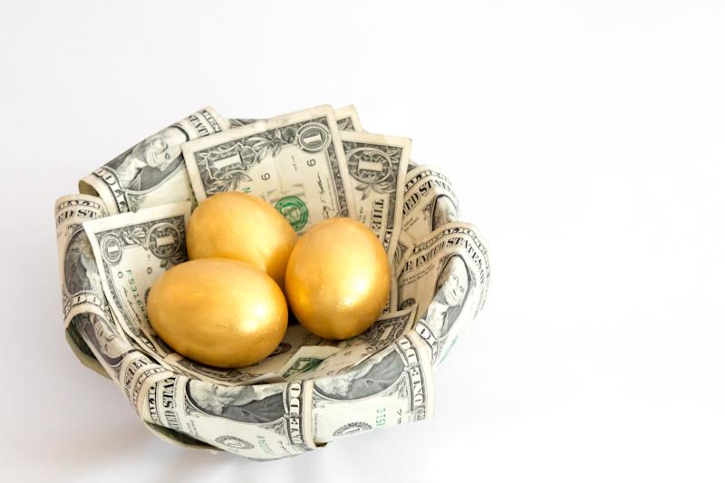 Three golden eggs in a basket lined with one-dollar bills.
