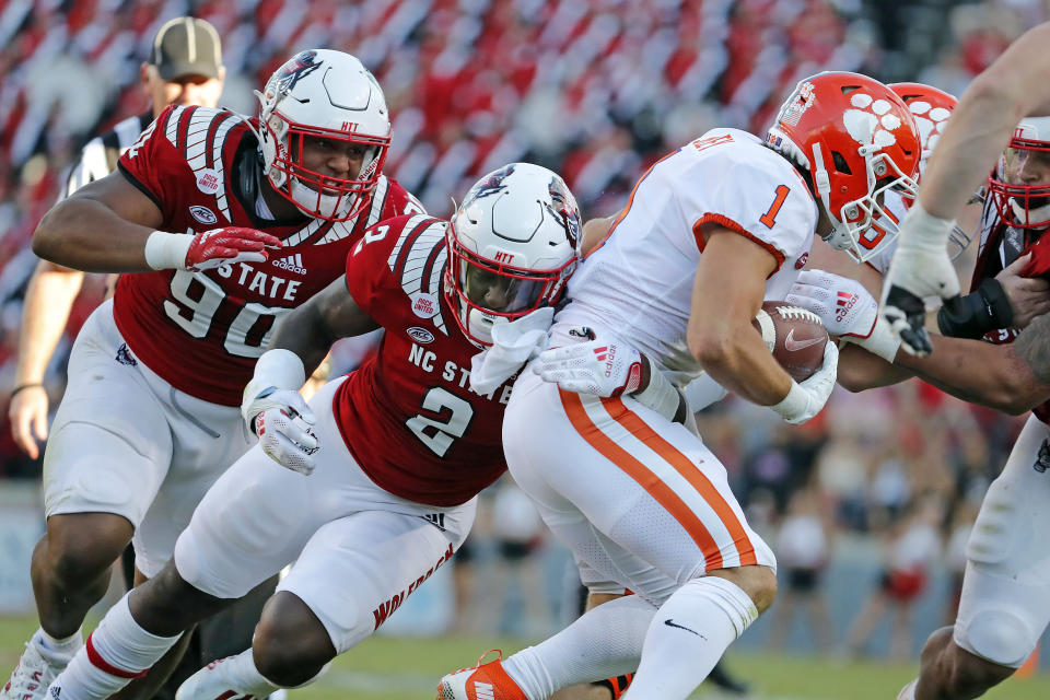 North Carolina State's Jaylon Scott (2) and Savion Jackson (90) tackle Clemson's Will Shipley (1) during the second half of an NCAA college football game in Raleigh, N.C., Saturday, Sept. 25, 2021. (AP Photo/Karl B DeBlaker)