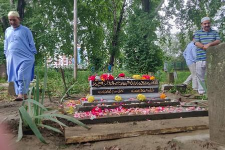 People leave after offering prayers at the grave of Mohammad Sikander Bhat, in Srinagar