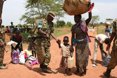 A Uganda People's Defence Forces (UPDF) soldier receives South Sudanese refugees crossing into Uganda at the Ngomoromo border post in Lamwo district, northern Uganda, April 4, 2017. REUTERS/Stringer