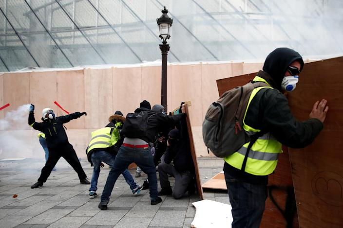 """Protesters wearing yellow vests face off with police forces during clashes on the Champs-Elysees Avenue during a national day of protest by the """"yellow vests"""" movement in Paris, France, Dec. 8, 2018. (Photo: Christian Hartmann/Reuters)"""