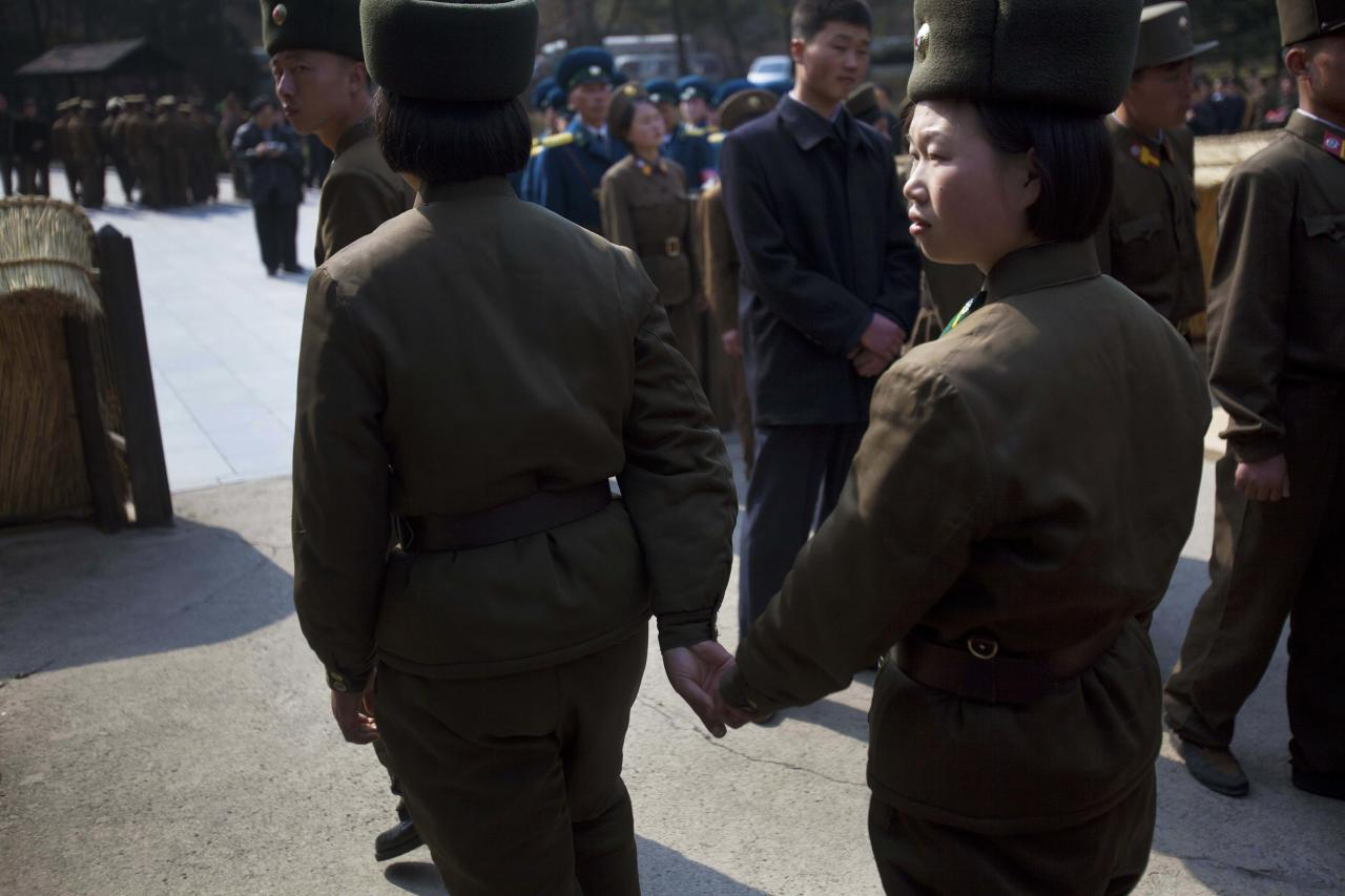 In this April 13, 2011 photo, two female North Korean soldiers hold hands as they tour the birthplace of Kim Il Sung at Mangyongdae, North Korea. (AP Photo/David Guttenfelder)