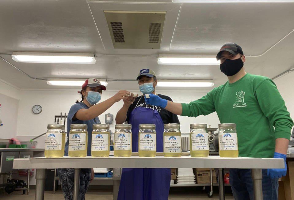 In this Nov. 10, 2020, photo provided by the Maniilaq Association, Maniilaq officials Joanna Barton, left, Cyrus Harris, center, and Chris Dankmeyer toast their first batch of approved seal oil made in Kotzebue, Alaska. In January 2021, the Alaska Department of Environmental Conservation approved seal oil to be served at the Maniilaq elder care home, believed to be a first for seal oil in the U.S. (Maniilaq Association via AP)