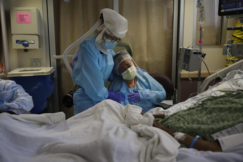 FILE - In this July 31, 2020, file photo, Romelia Navarro, right, is comforted by nurse Michele Younkin as she weeps while sitting at the bedside of her dying husband, Antonio, in St. Jude Medical Center's COVID-19 unit in Fullerton, Calif. California's coronavirus death toll reached 70,000 people, on Monday, Oct. 11, 2021. (AP Photo/Jae C. Hong, File)