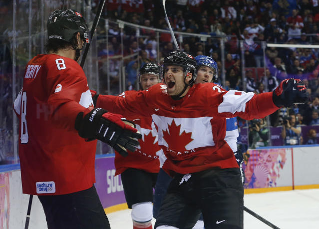 Canada forward John Tavares, right, and forward Jeff Carter, second from left, celebrate with defenseman Drew Doughty (8) after Doughty scored a sudden death overtime goal against Finland during a men's ice hockey game at the 2014 Winter Olympics, Sunday, Feb. 16, 2014, in Sochi, Russia. Canada won 2-1. (AP Photo/Mark Humphrey)