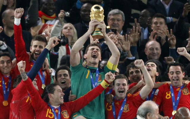 "FILE _ This is a file photo of Spain's goalkeeper Iker Casillas, center, as he holds up the World Cup trophy with team members as they celebrate their victory at the end of the World Cup final soccer match between the Netherlands and Spain at Soccer City in Johannesburg, South Africa. Winning the soccer World Cup can bring instant rewards to that country's stock market investors. But they better be quick as the post-victory rally doesn't last long. That's the conclusion of investment bank Goldman Sachs, which published a wide-ranging report late Tuesday May 27, 2014 on the World Cup and its economic impact. Goldman Sachs analysts found ""a clear pattern of out performance by the wining team in the weeks after the World Cup final."" On average, the investment bank's portfolio strategy team the victor outperforms the global market by 3.5 percent in the first month. (AP Photo/Luca Bruno, File)"