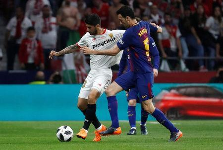 Soccer Football - Spanish King's Cup Final - FC Barcelona v Sevilla - Wanda Metropolitano, Madrid, Spain - April 21, 2018 Barcelona's Sergio Busquets in action with Sevilla's Ever Banega REUTERS/Juan Medina