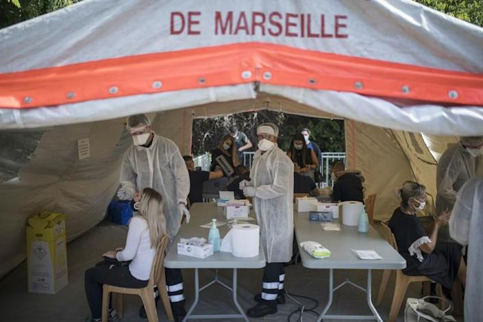 FILE - In this Sept. 24, 2020, file photo, people receive COVID-19 tests at a mobile testing center in Marseille, France. The worldwide death toll from the coronavirus eclipsed 1 million, nine months into a crisis that has devastated the global economy, tested world leaders' resolve, pitted science against politics and forced multitudes to change the way they live, learn and work. (AP Photo/Daniel Cole, File)